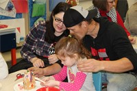 adults helping student decorate gingerbread house
