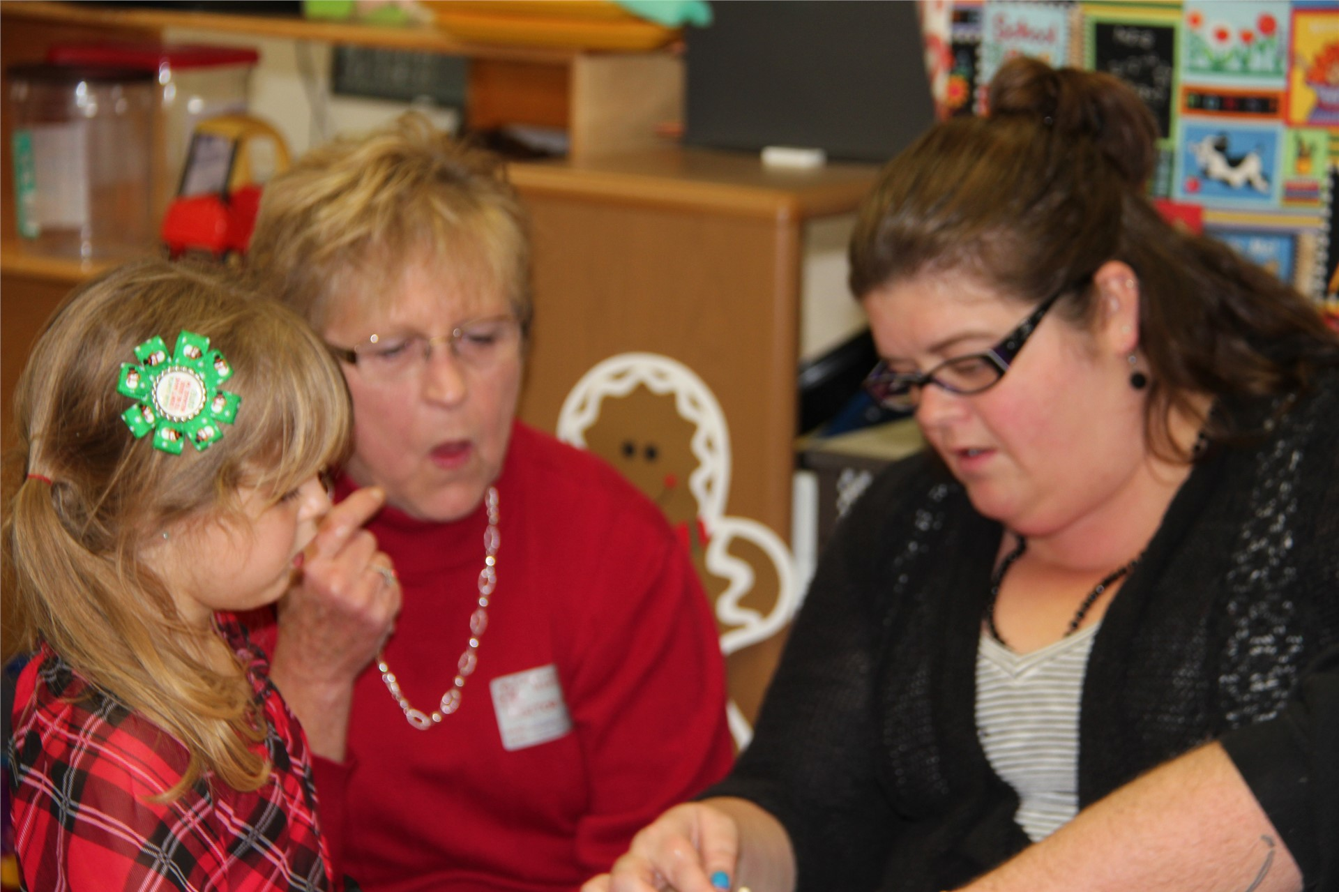 two adults helping student with gingerbread house