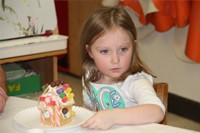student sitting next to gingerbread house