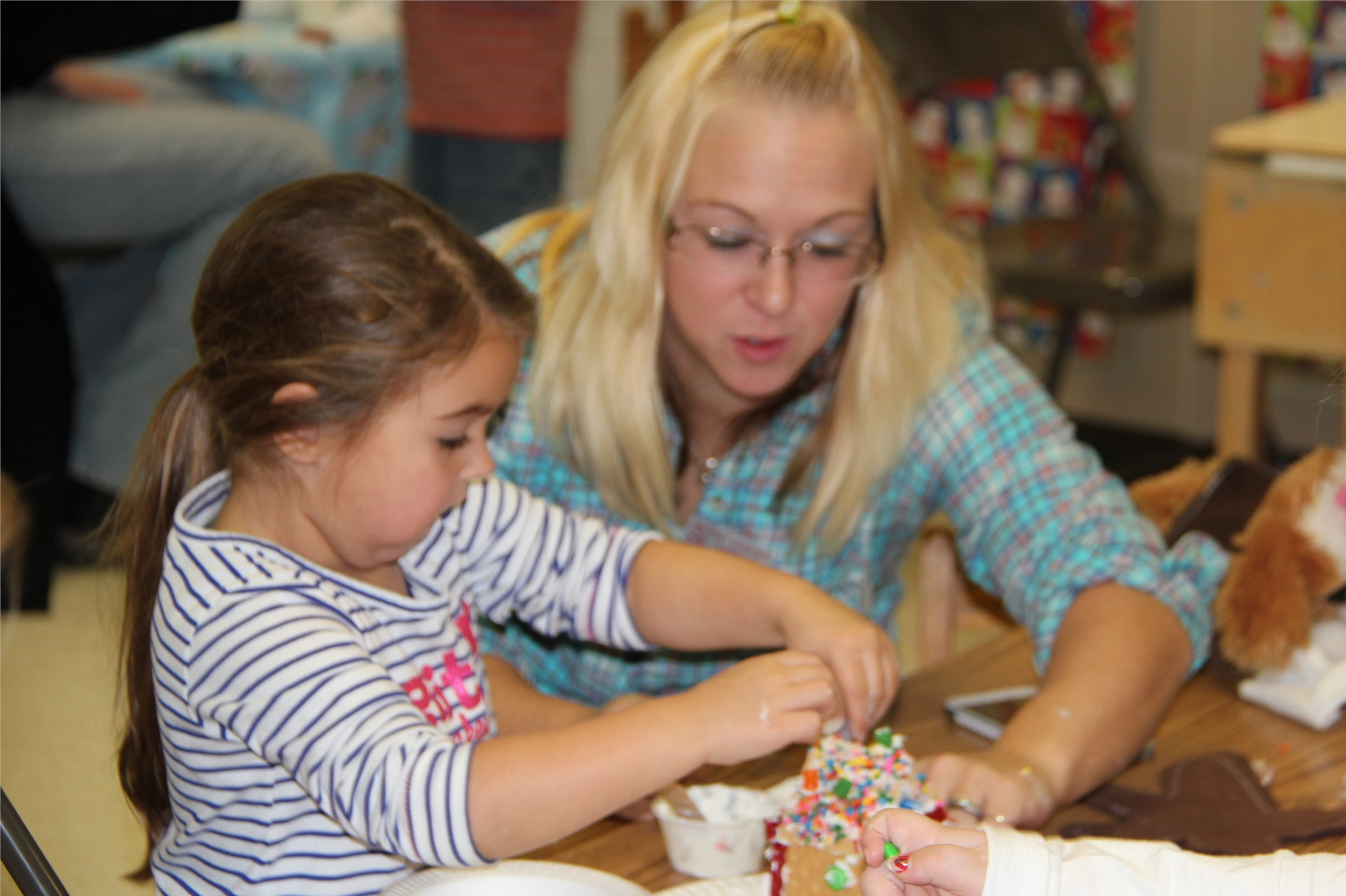 adult helping student with gingerbread house
