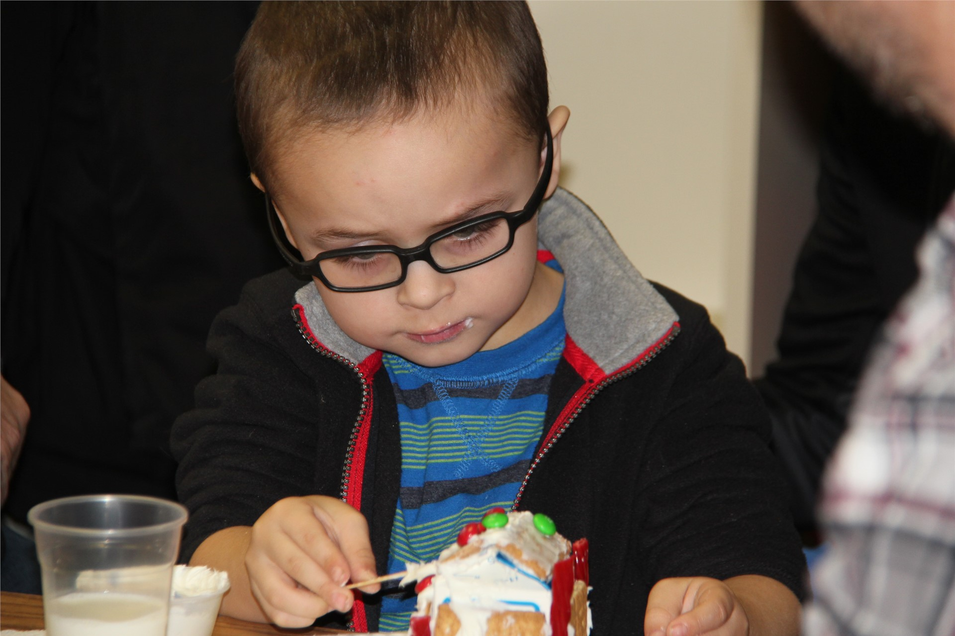 student frosting gingerbread house