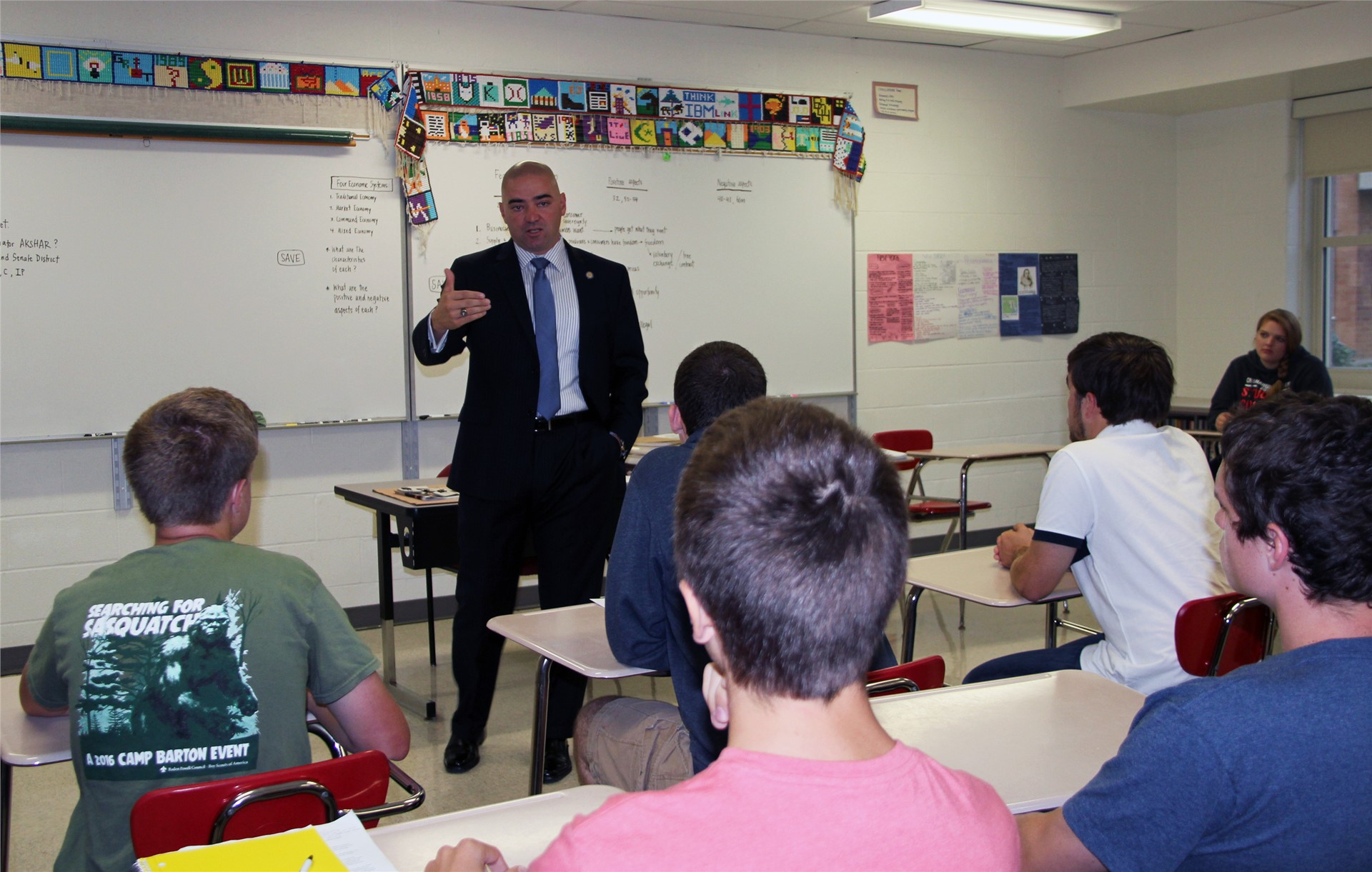 wide shot of senator akshar talking to students in classroom