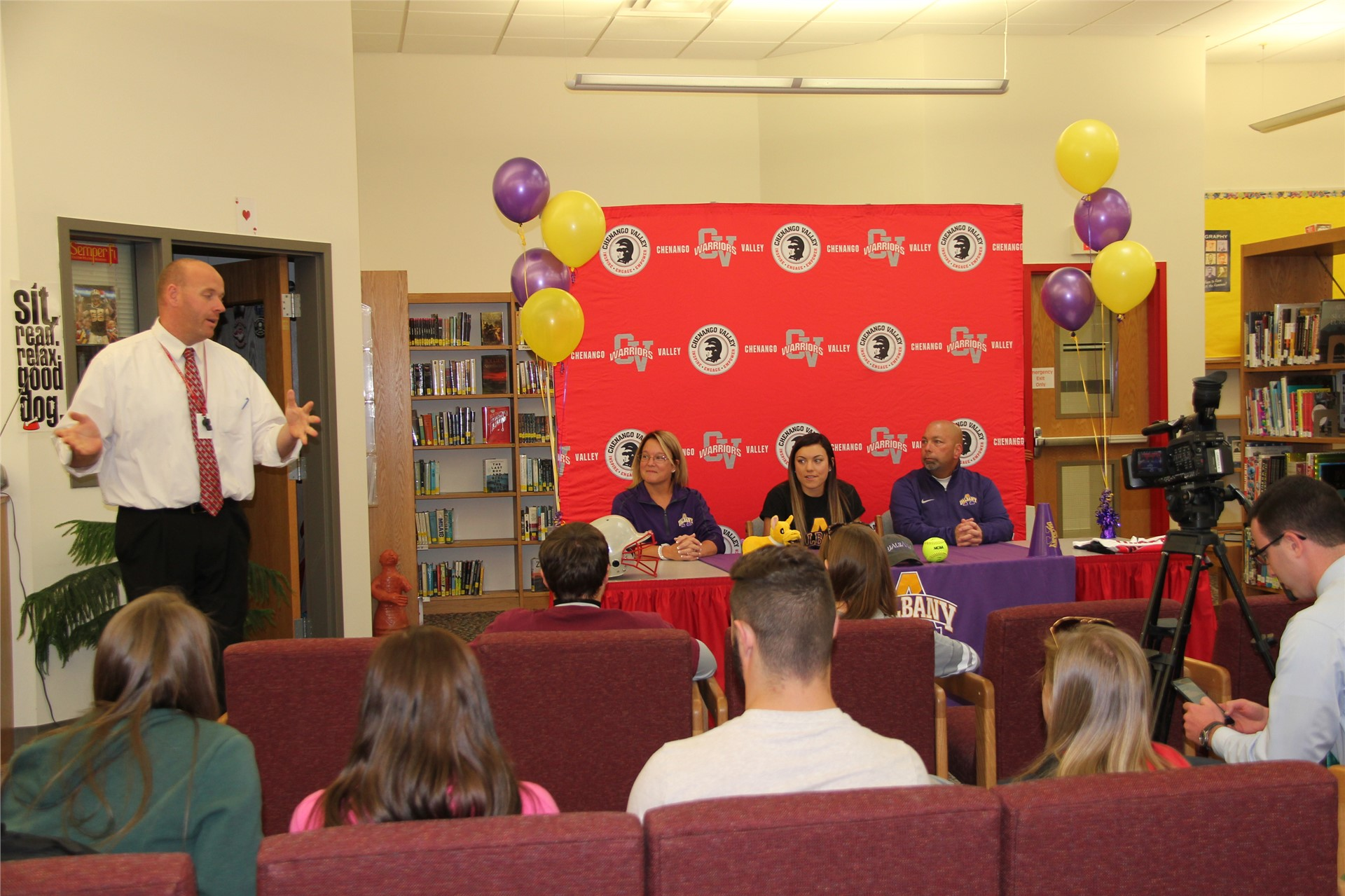 wide shot of student signing with mister tomm standing speaking