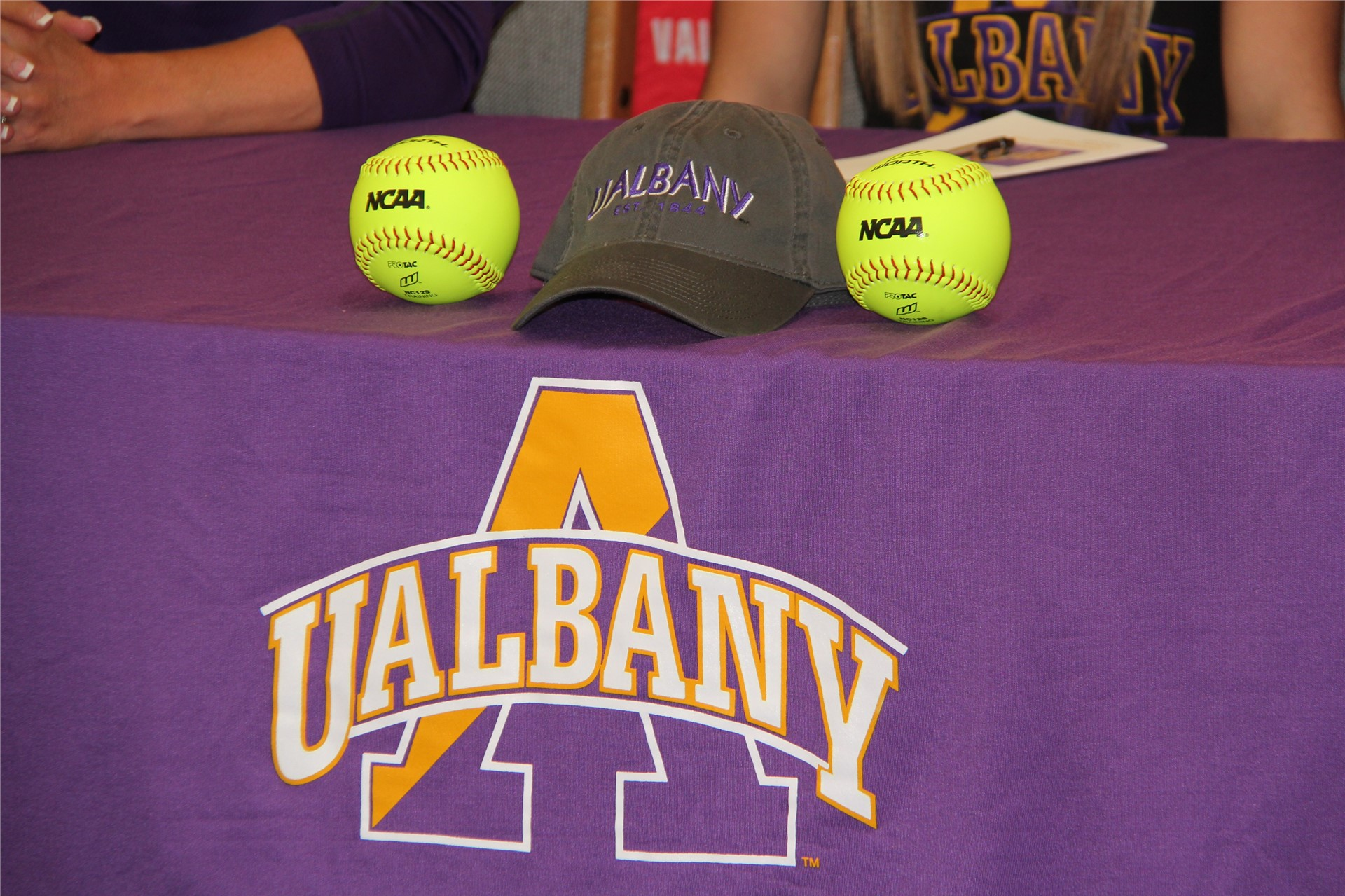 table says u albany with hat and two softballs on it