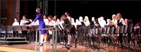 band and teacher stand on stage
