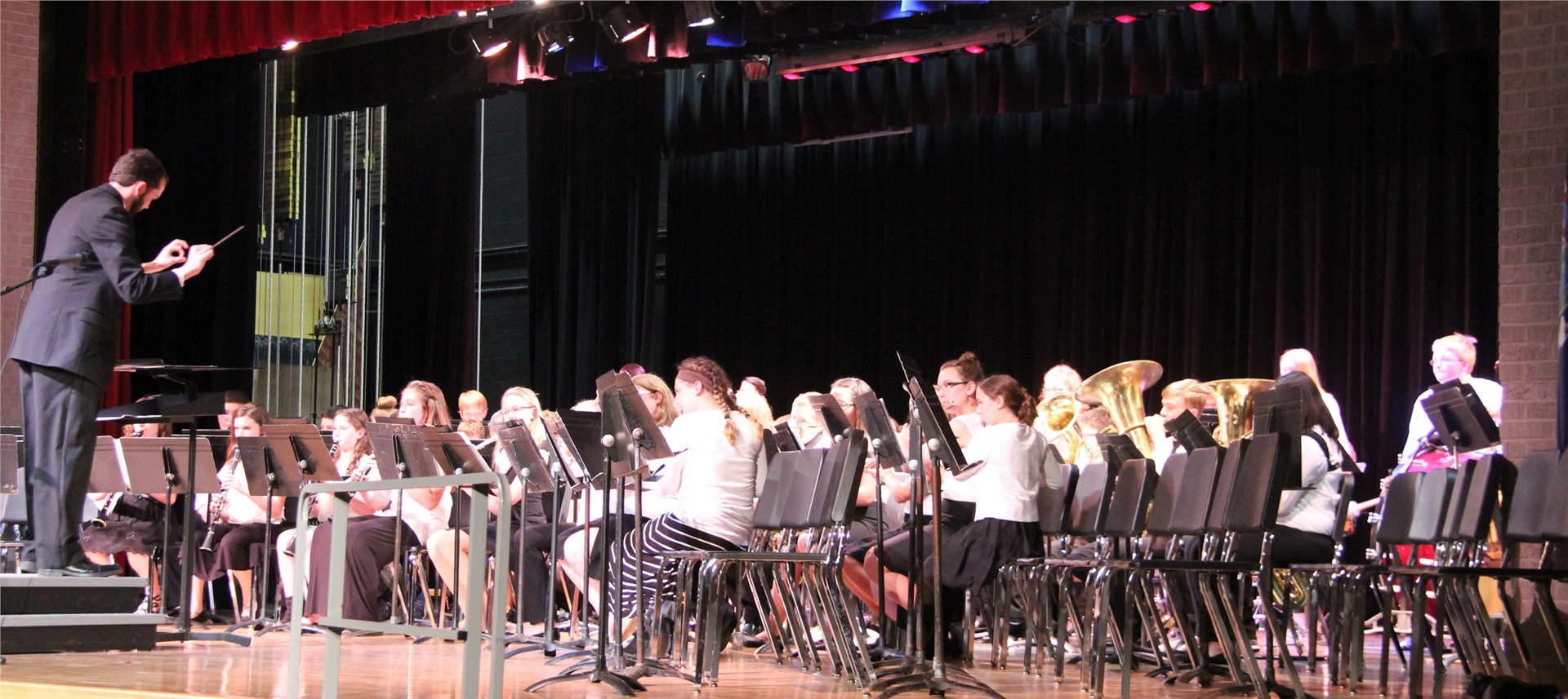 students play band instruments while teacher conducts