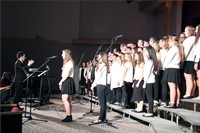 wide shot of student singing at microphone