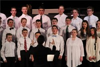 wide shot of students singing with teacher conducting