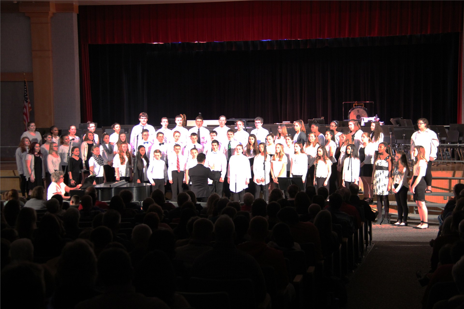 far shot of students singing with teacher conducting