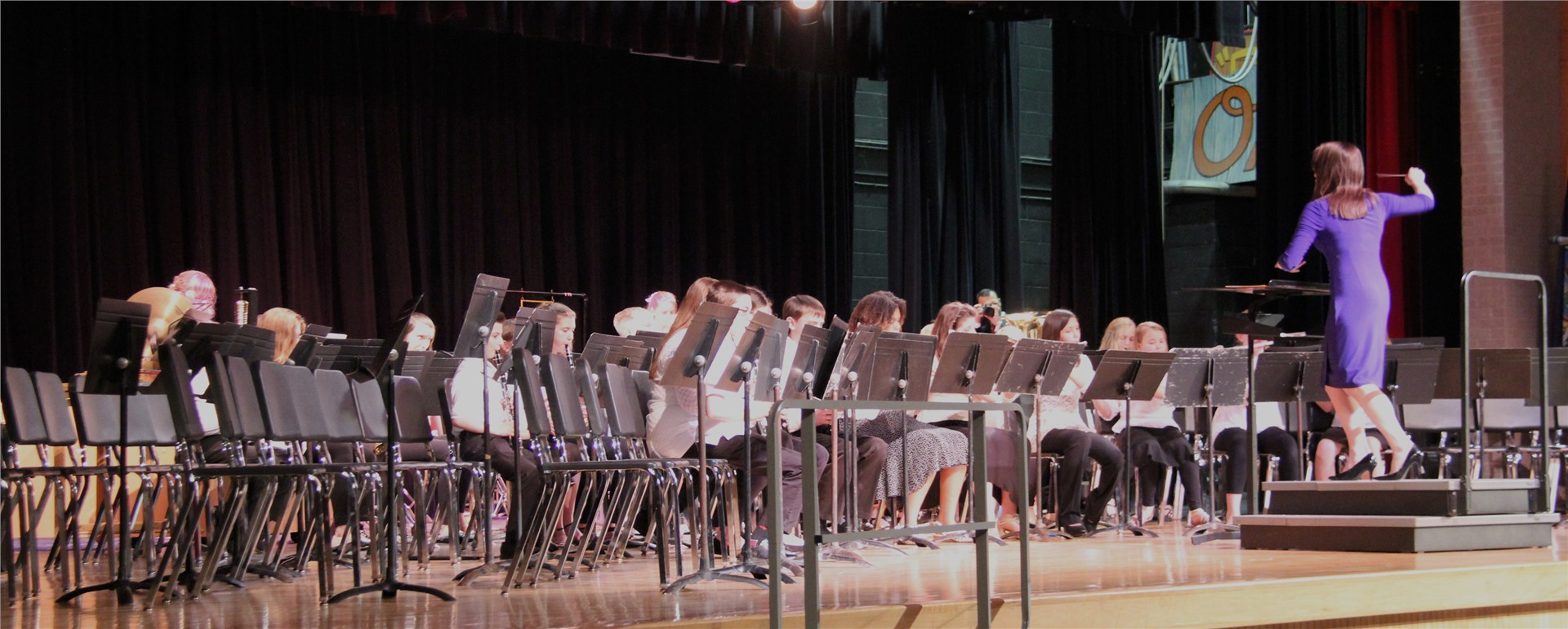 students playing instruments while teacher conducts band