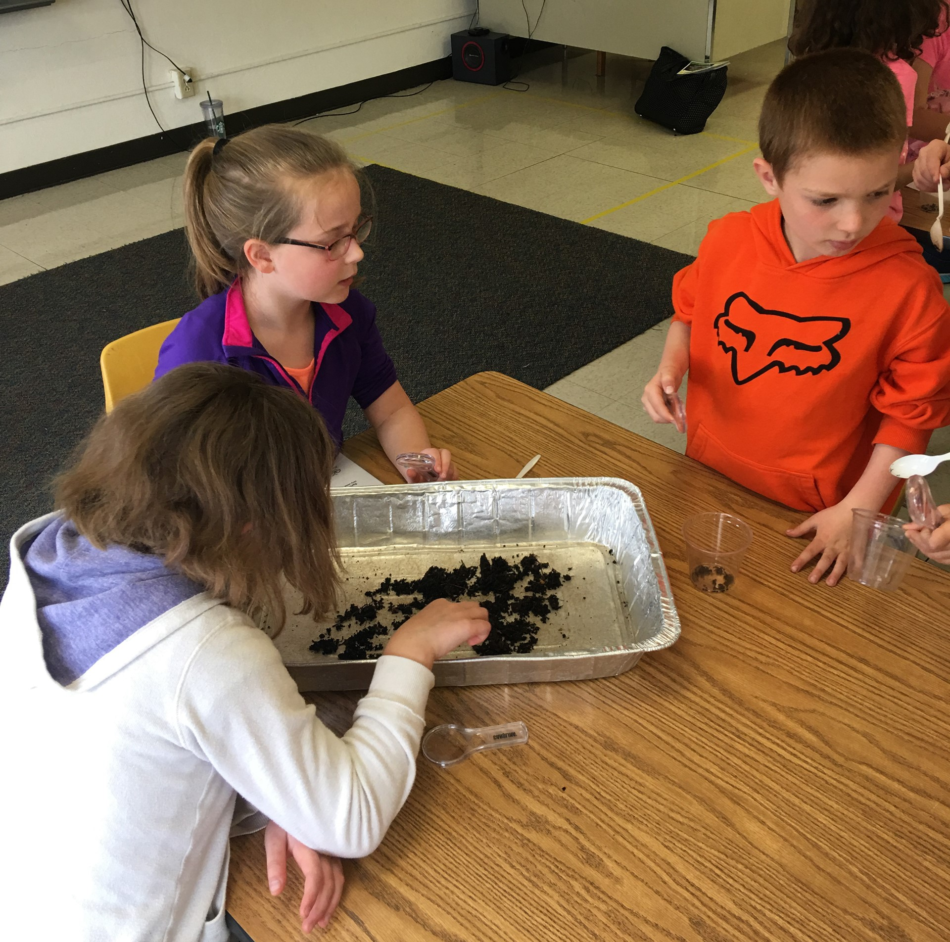 students at table with compost materials