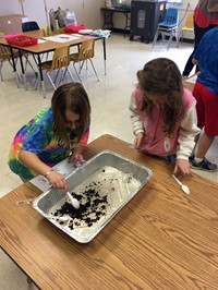 student sifts through compost material