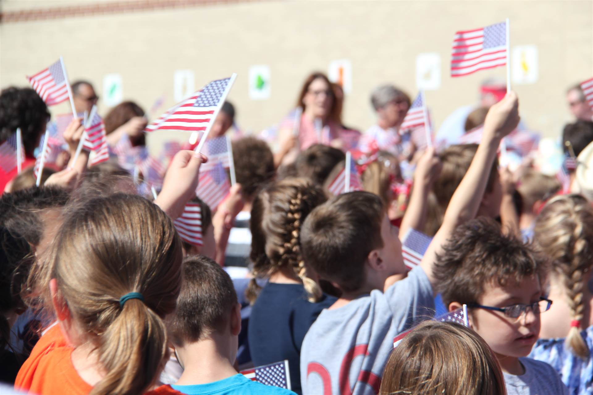 Elementary students wave small flags in the air at annual Flag Day event