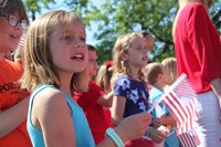girl waves small flag and sings at annual Port Dickinson Flag Day event