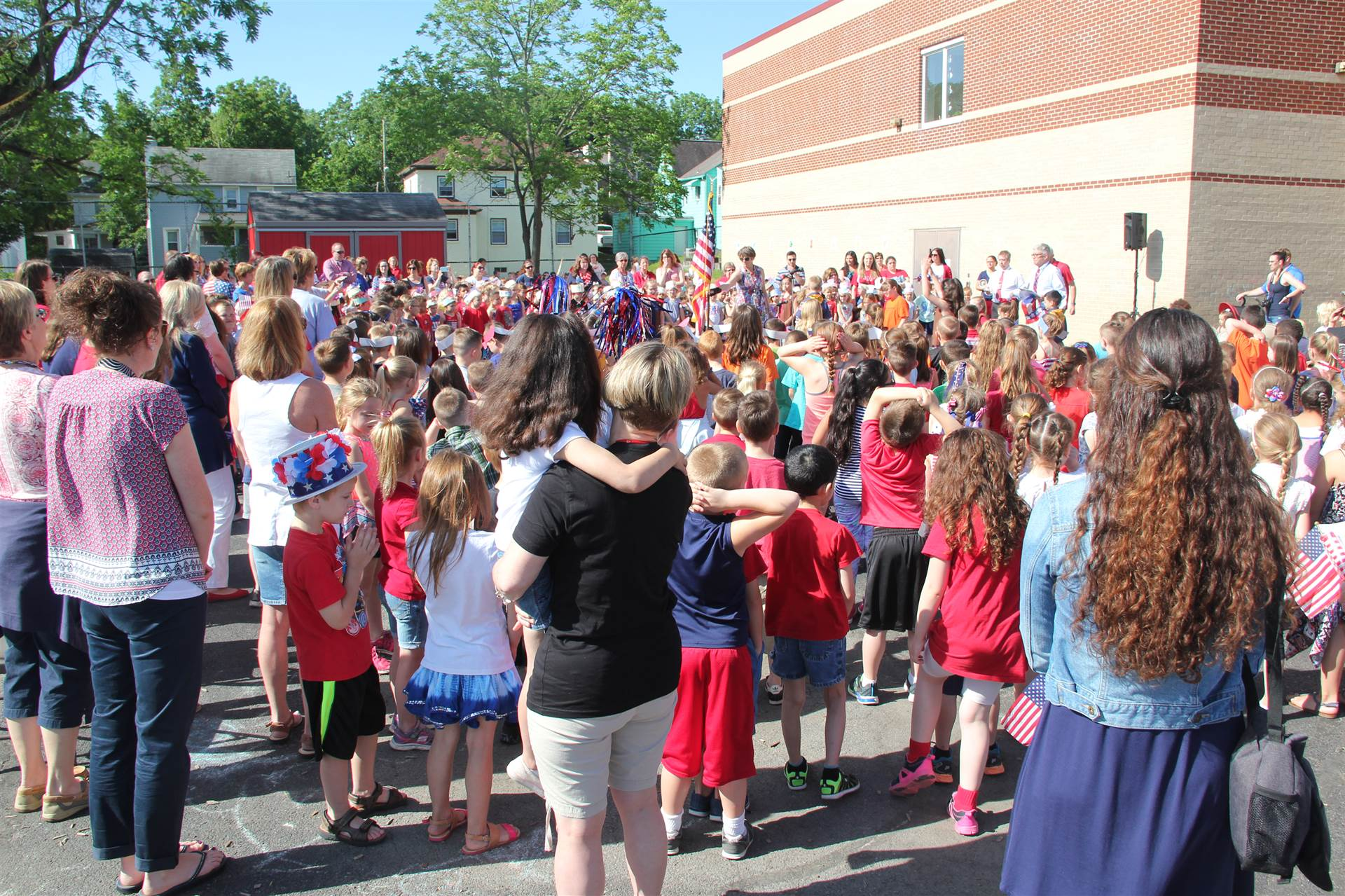 wide shot of annual port dickinson flag day event held behind elementary school building