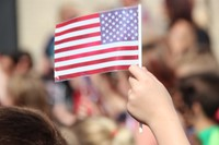 up close of hand waving small American flag