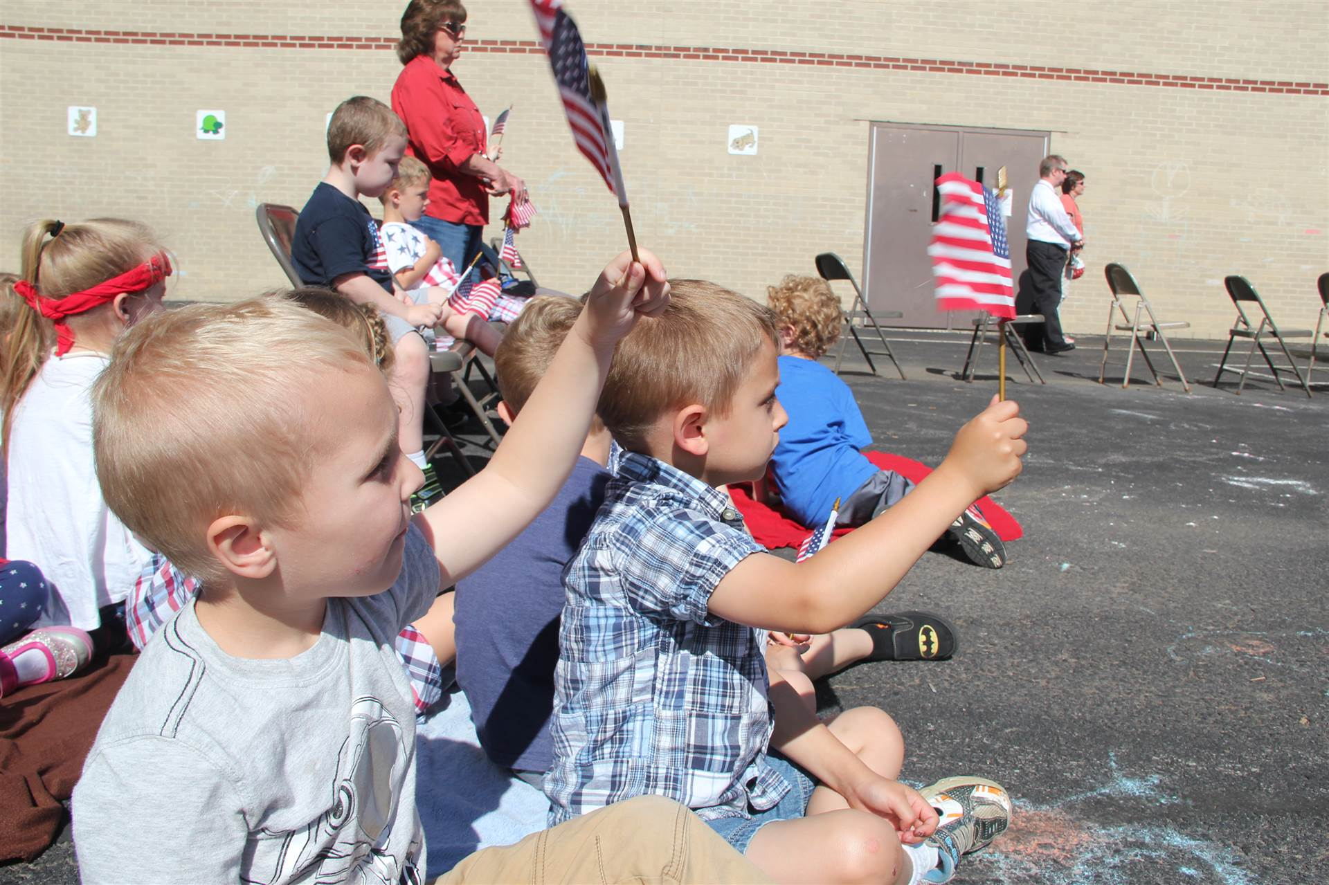 young students wave small American flags at annual Port Dickinson Flag Day event