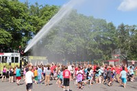 side angle of fire hose spraying children