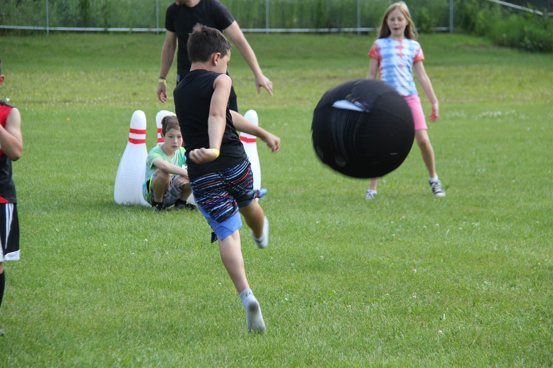 boy kicks ball for an inflatable bowling game