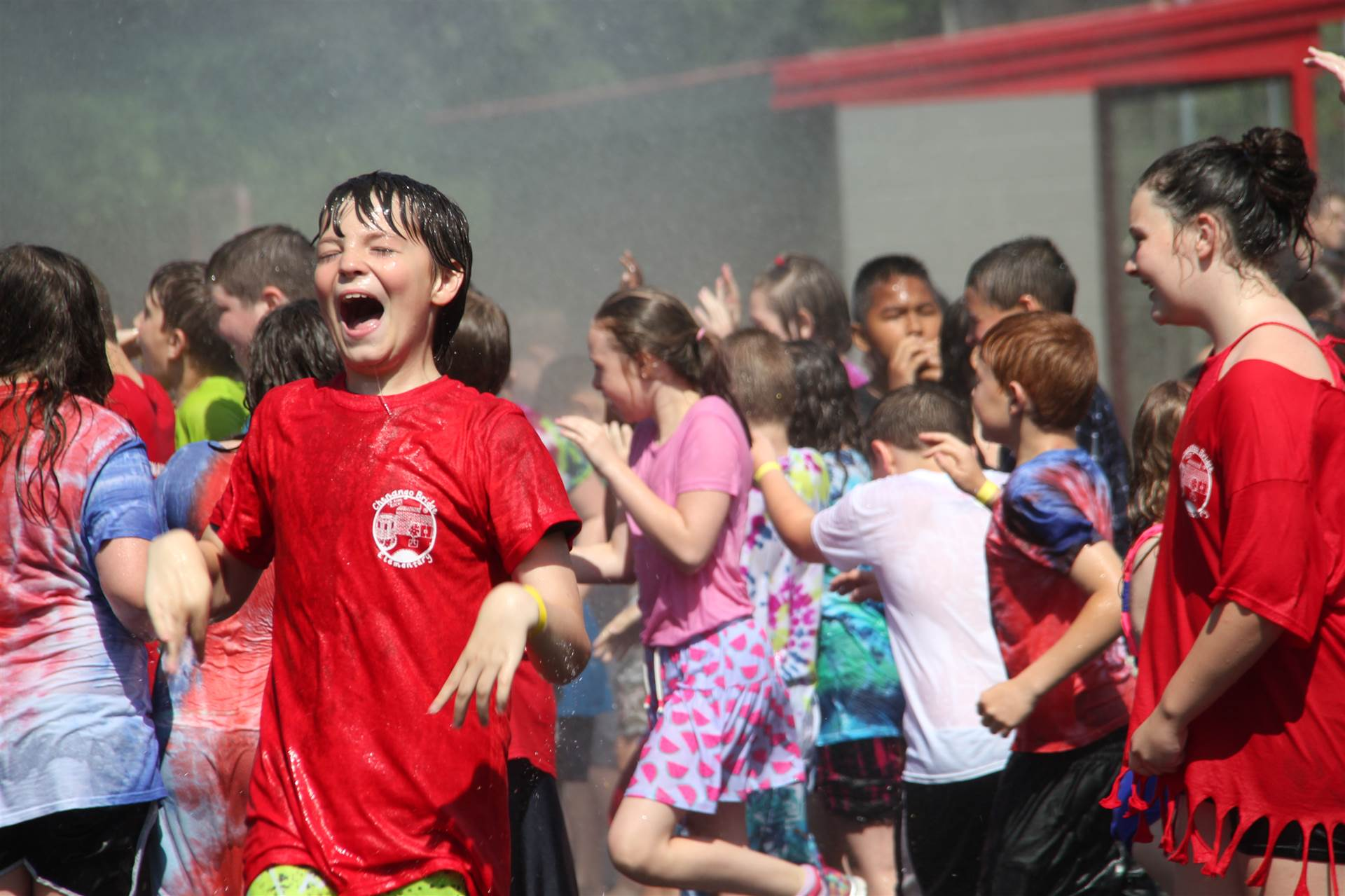 children laugh in the water from the hose