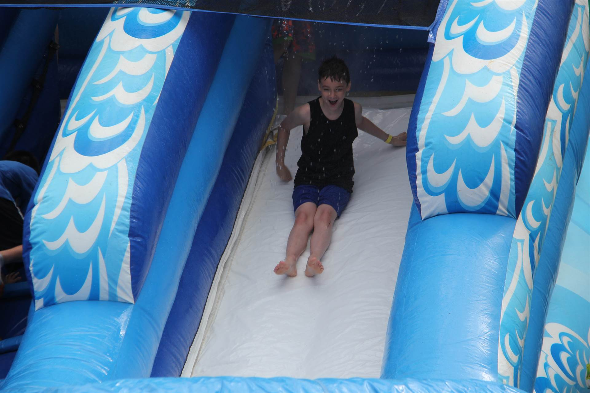 boy going down inflatable water slide