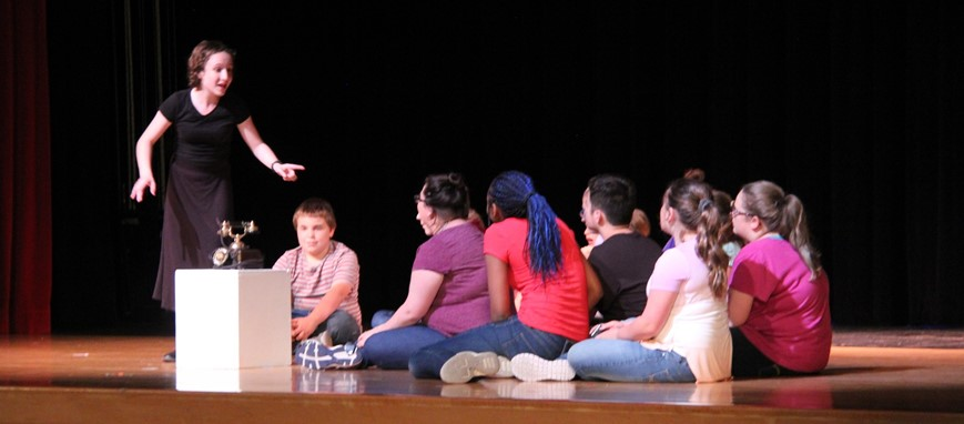 Middle Schoolers act on stage in drama club play