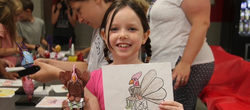 Girl poses with monster drawing that was turned into a 3 d clay sculpture for monster mash event