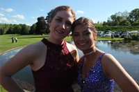Girls pose for prom picture in front of pond