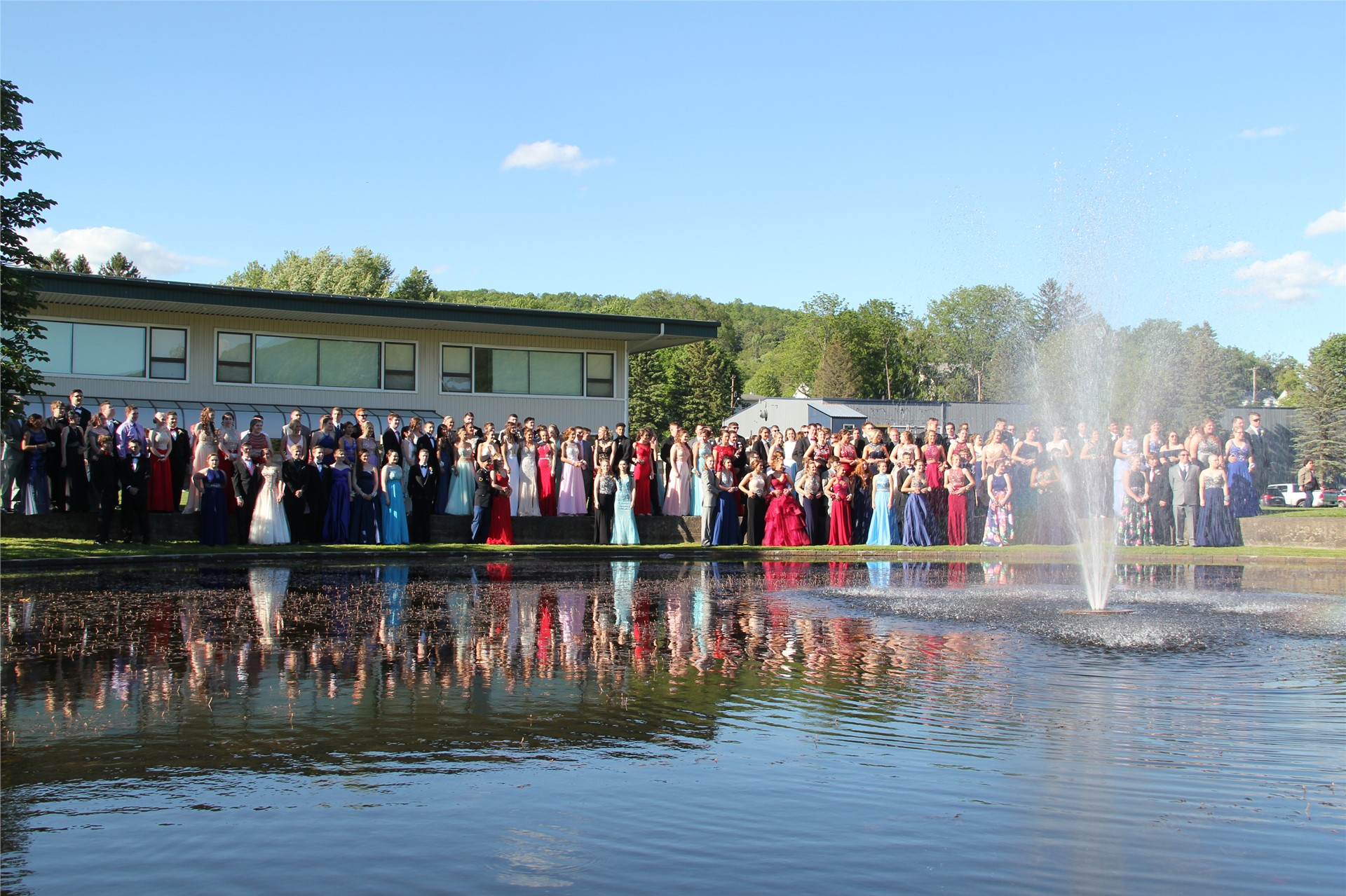 Far away shot of large group of students standing behind pond for a photo before prom starts