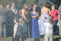 Distance shot of group of students posing for pictures before prom