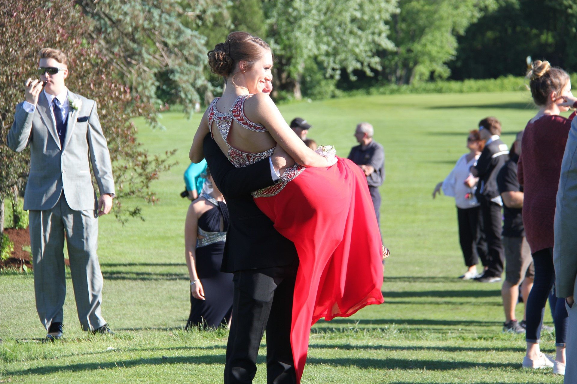 Student carries prom date in arms as they pose for picture before prom