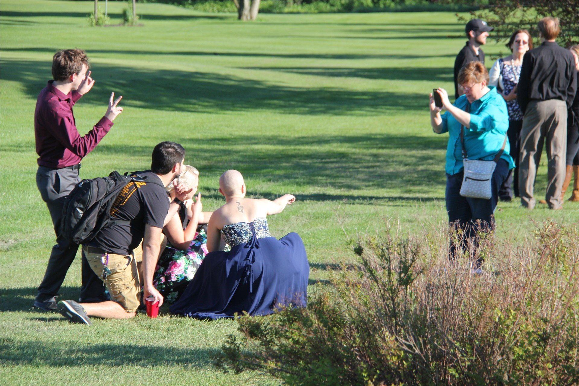 Far away shot of students posing with friends for pictures before prom starts