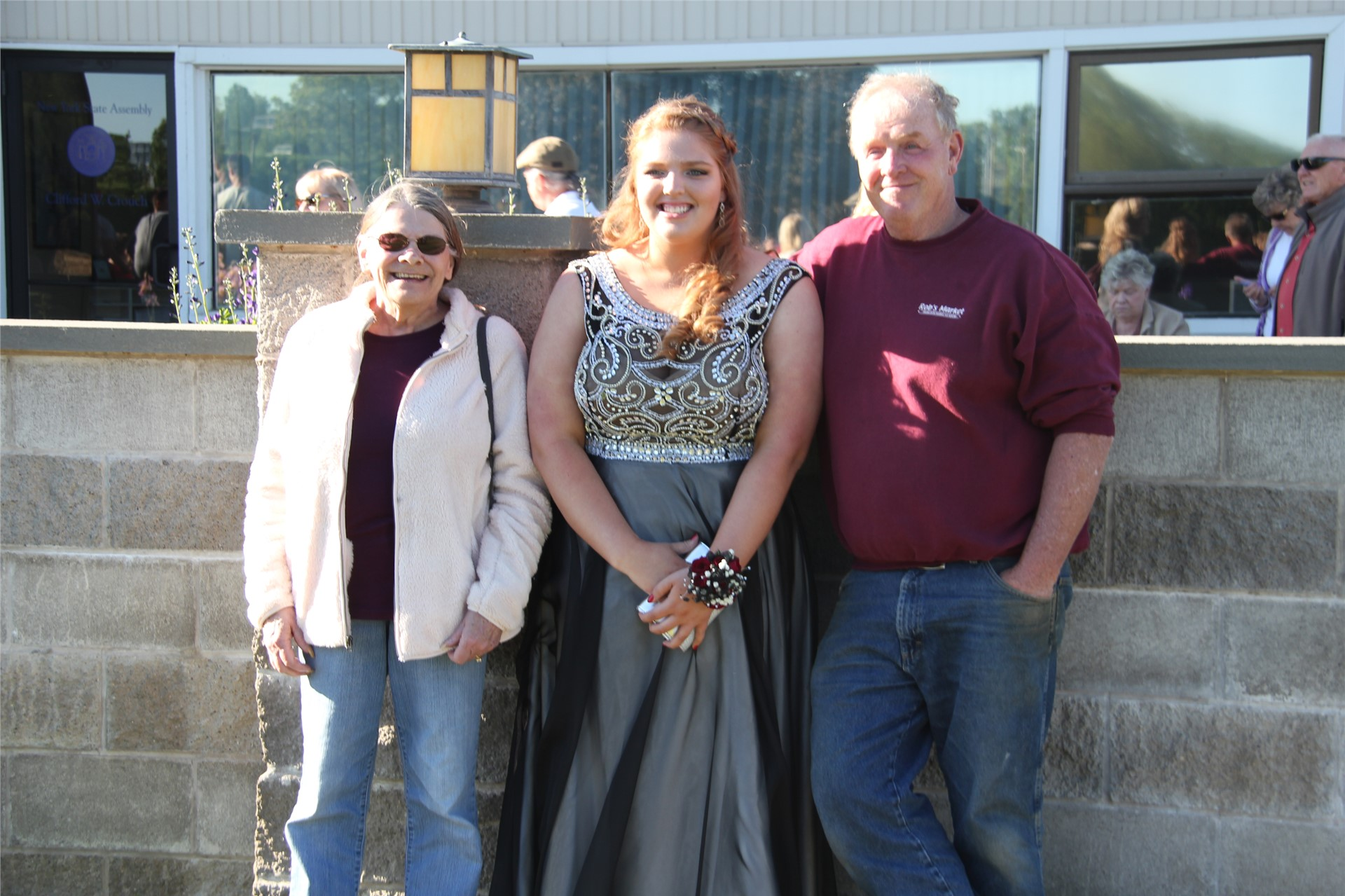 Female student poses with two family members for picture before prom starts