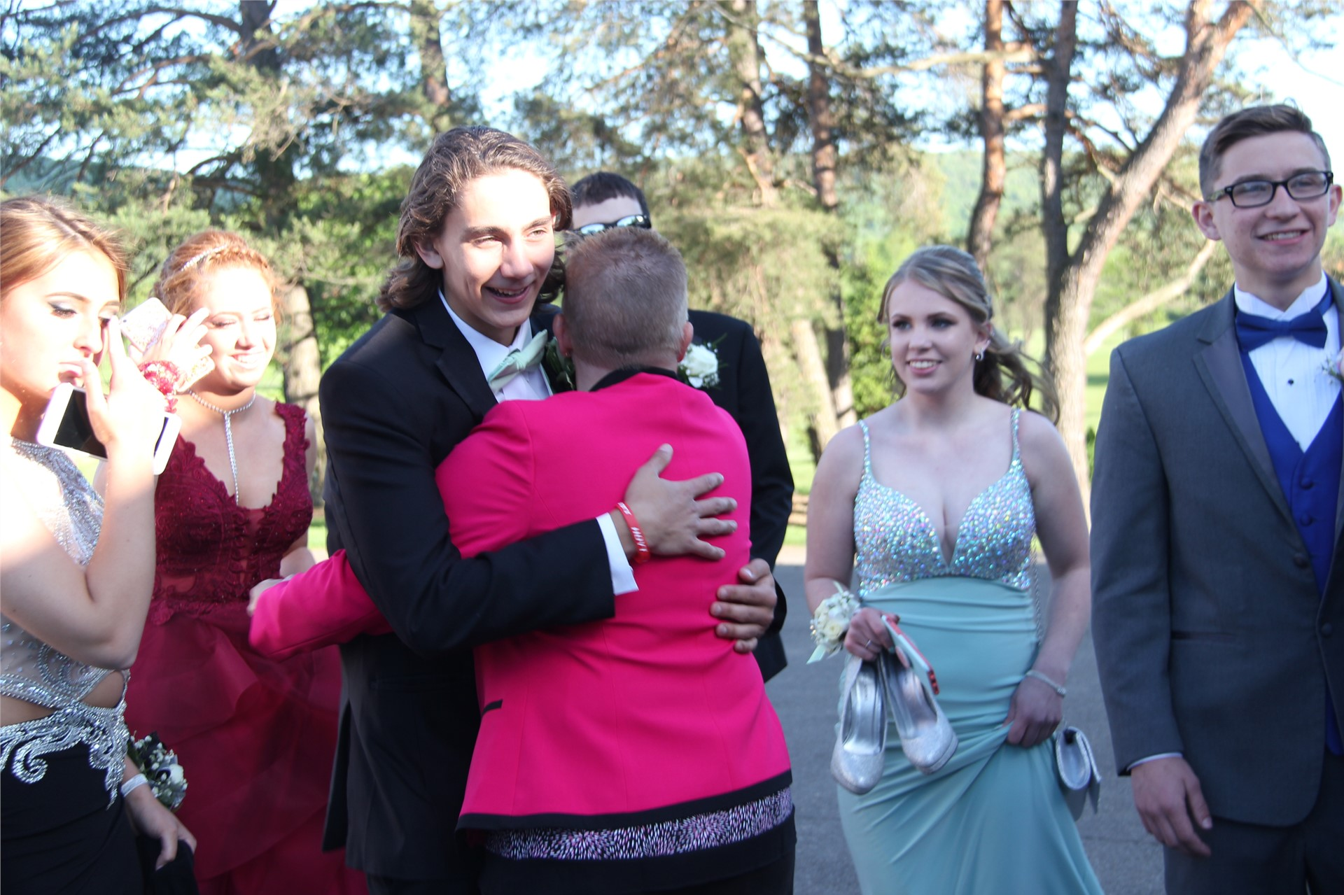 teacher hugs student who is about to go into prom