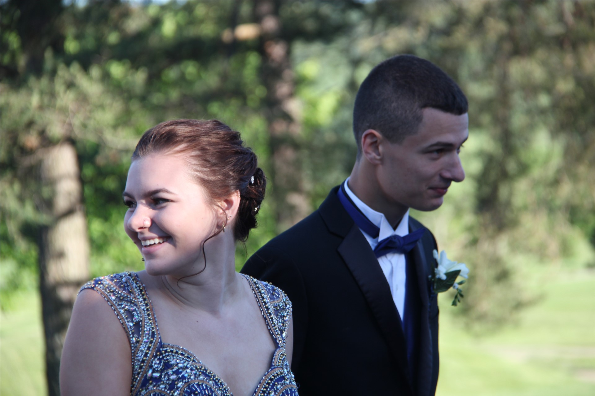 prom dates smile while standing in line to get into prom