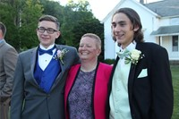 two male students smile for photo with female teacher standing in the middle