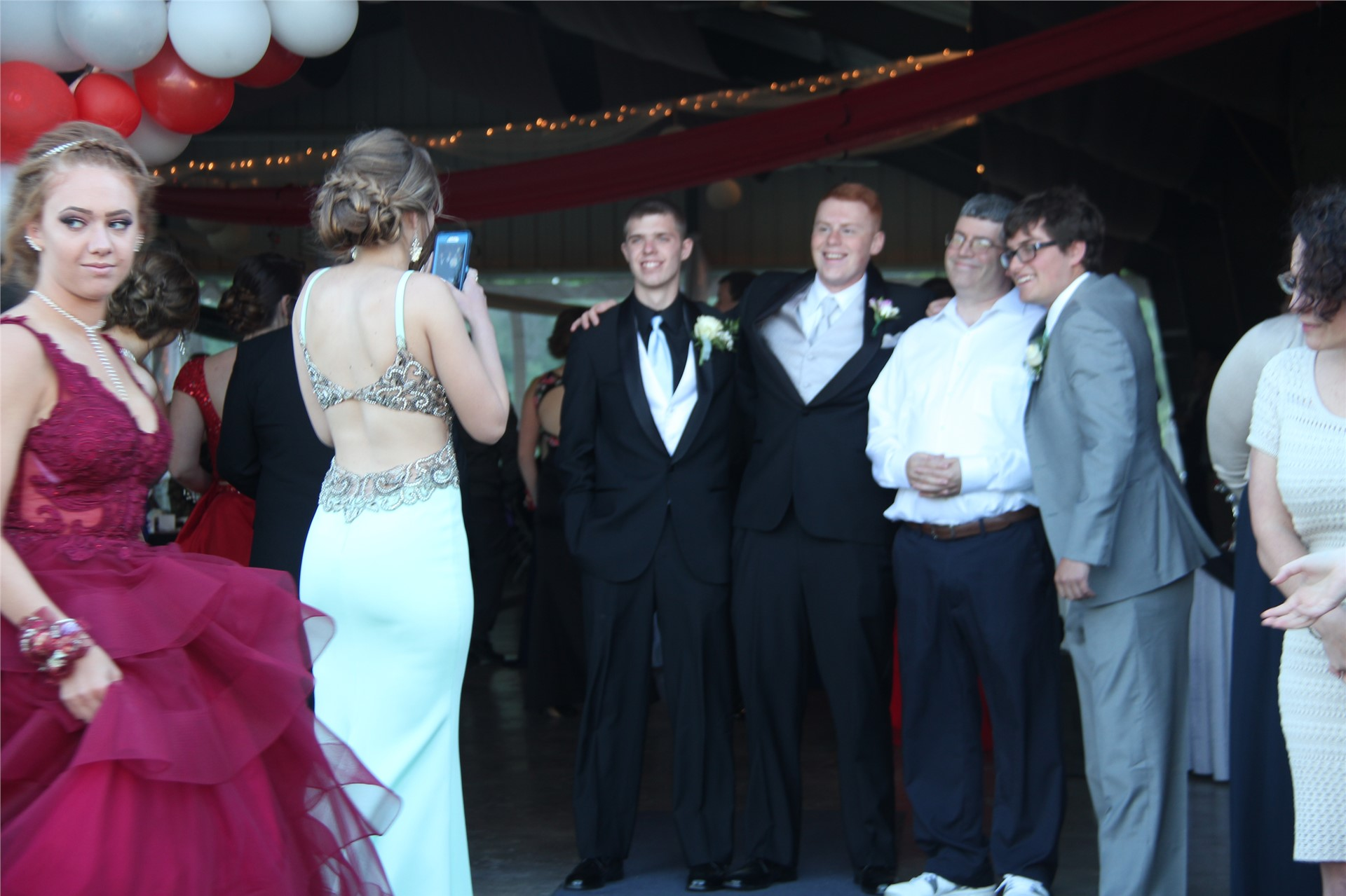 female student takes a photo of four male students posing at prom