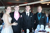 group of four students stand posing for picture inside prom event