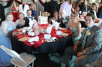table of students sit posing for picture at prom