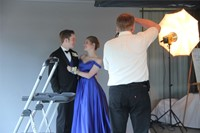 professional photographer takes a photograph of posing prom dates