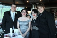 group of four students stand for picture inside prom event