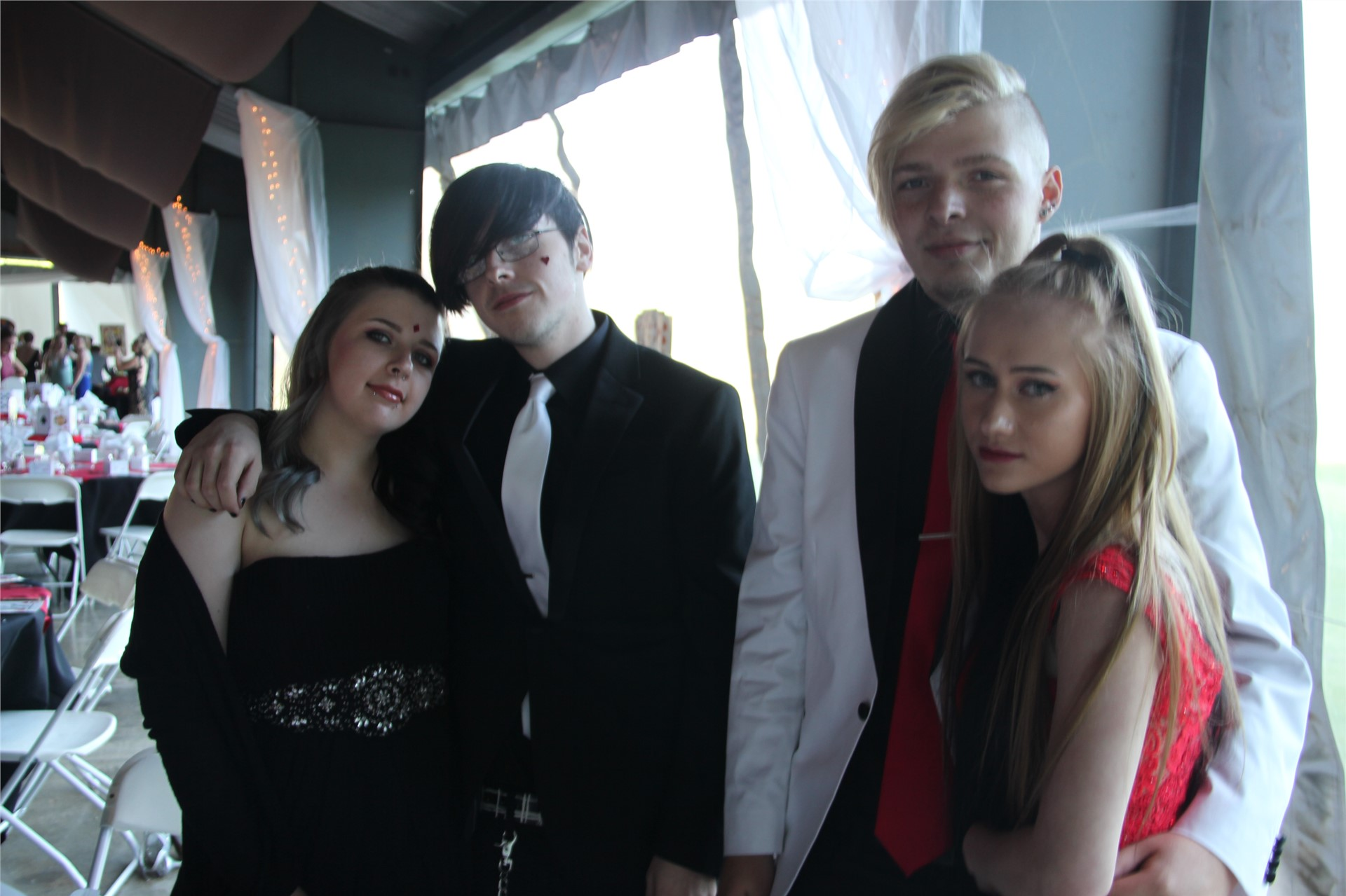 Two sets of prom dates pose for photo inside prom event