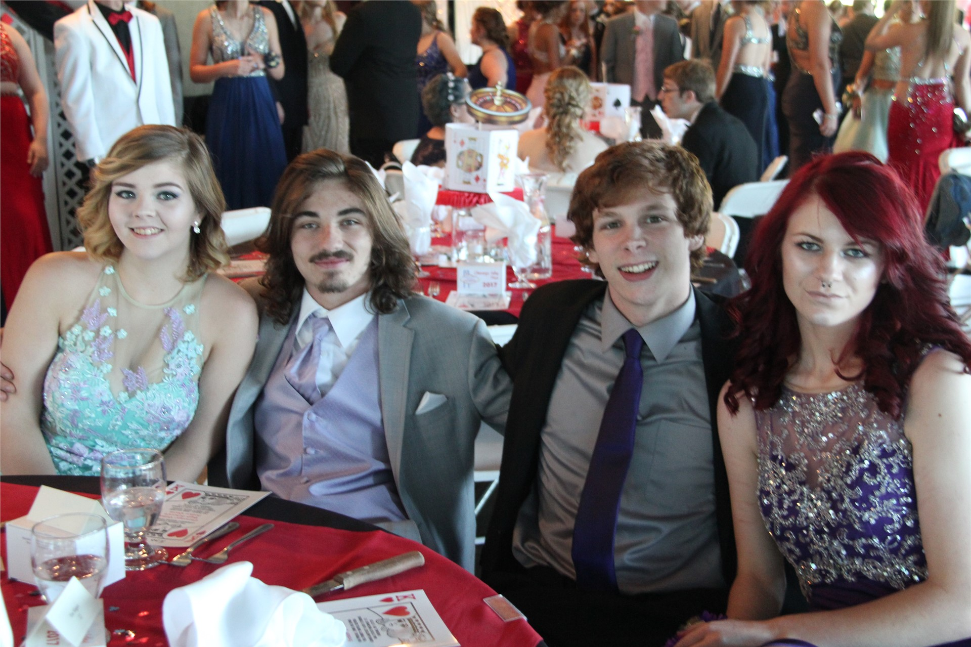 four students pose sitting for picture at prom