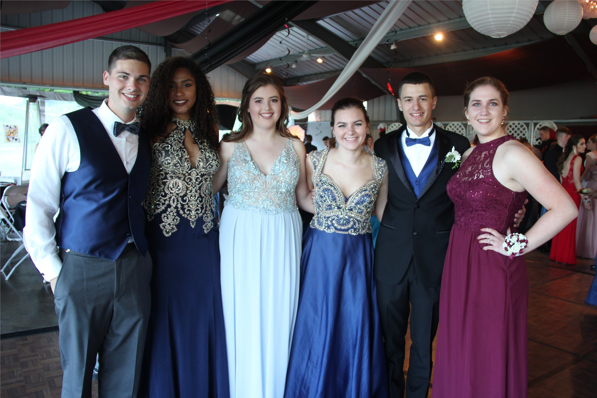 group of six students pose for a photo inside of prom event