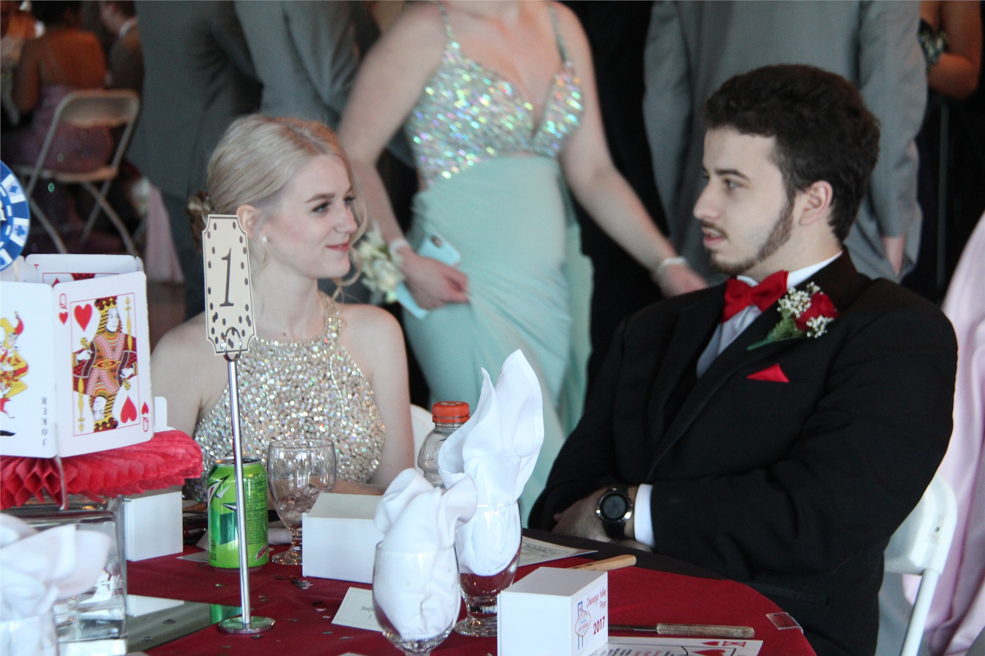 male and female student talk while sitting at table