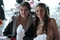 two female students pose sitting for a picture at prom