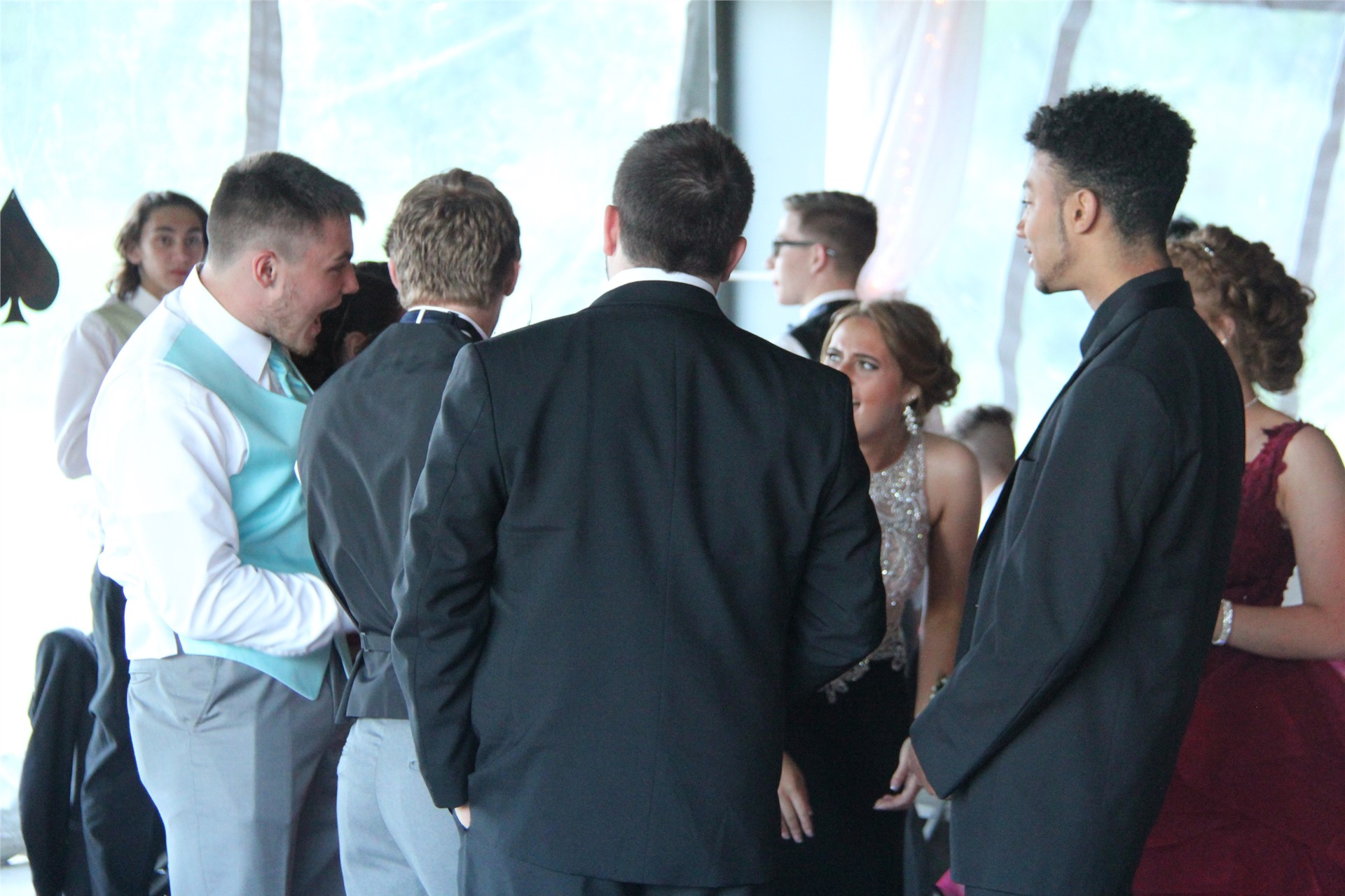 group of male students talk inside prom