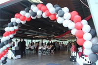 red, white, and black balloons make arch at entrance of the venue