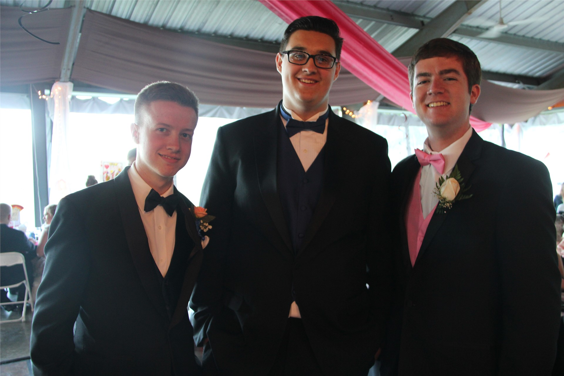 three male students pose standing and smiling for a picture