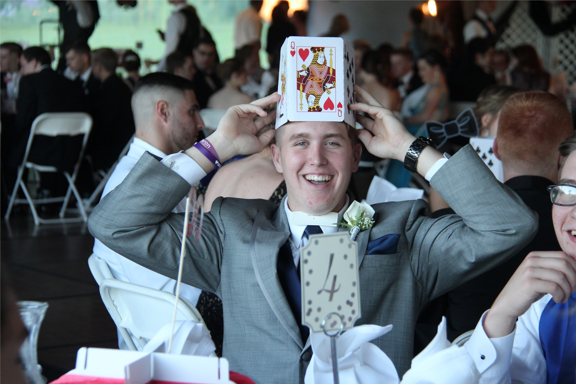 student laughing wears a hat made of cards